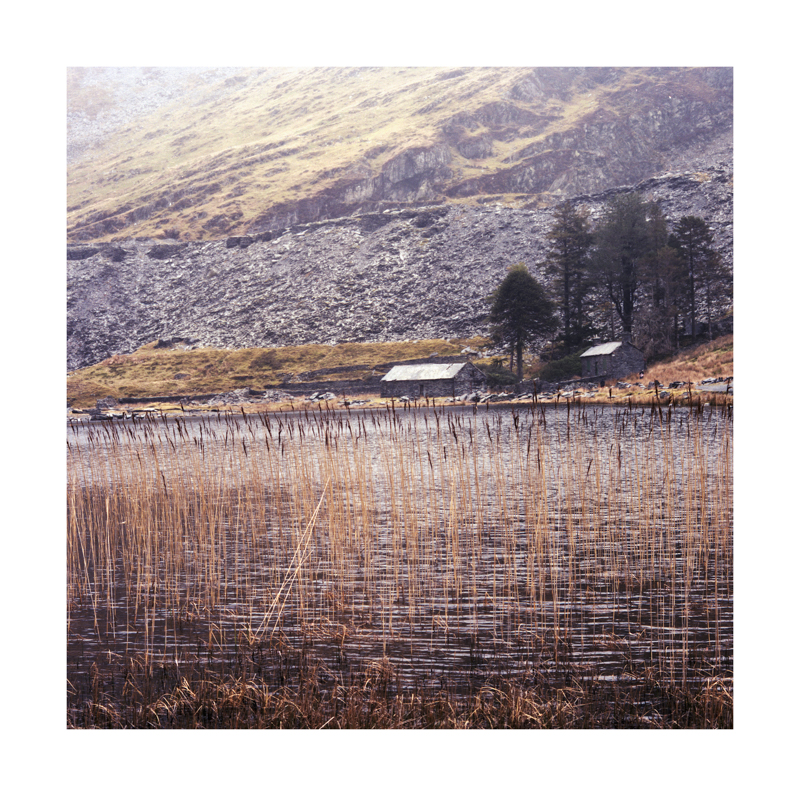 A view of some reeds, the lake and an abandonded building at Cwmorthin Quarry, North Wales